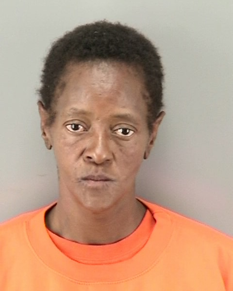Booking photo of black female, Jacqueline Miller in orange shirt.
