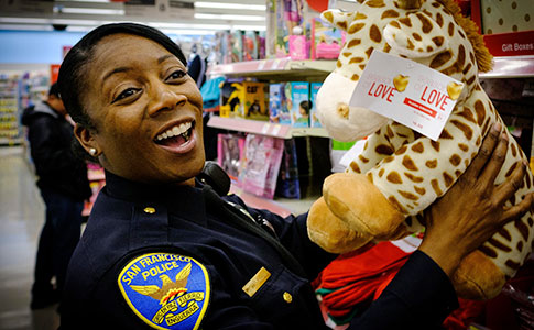 SFPD Female Officer holding stuffed animal toy