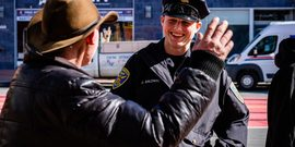 SFPD officer smiling at man wearing cowboy hat