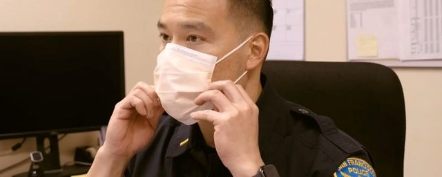 Picture of officer putting on mask